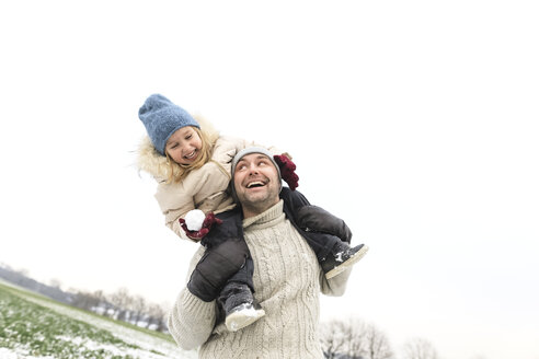 Playful father carrying daughter piggyback in winter landscape - KMKF00699