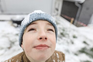 Boy looking up on falling snow - KMKF00711
