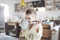 Portrait of little girl with smartphone drinking tea in the kitchen - KMKF00714