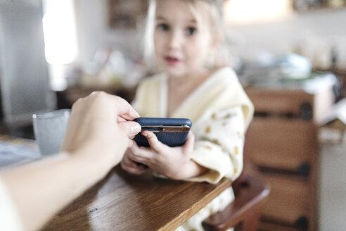 Wickede, NRW, Deutschland. Ein kleines Mädchen trinkt Tee und schaut im Smartphone an - KMKF00717