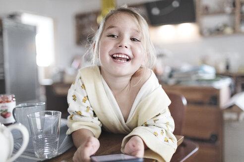Wickede, NRW, Deutschland. Ein kleines lachendes Mädchen sitzt in der Küche mit einem Smartphone - KMKF00720