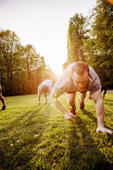 Friends exercising on grassy field in park - ASTF02248