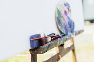 Paintbrushes and palette on easel outside studio - ASTF02290