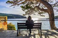 Spain, Mallorca, Sant Elm, woman sitting on bench, rear view - THAF02409