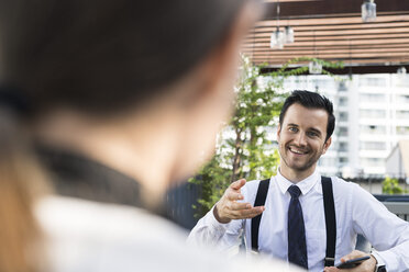 Smiling businessman talking to colleague on city terrace - SBOF01545