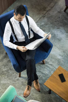 Top view of businessman sitting in blue armchair reading newspaper - SBOF01560