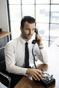 Businessman in office using vintage retro telephone - SBOF01569