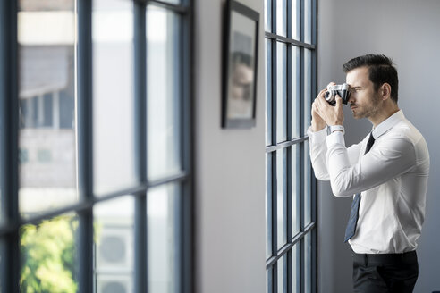 Businessman taking picture with vintage retro camera in front of large office window - SBOF01575