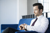 Businessman sitting on blue couch in office checking smartwatch - SBOF01578