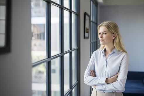 confident business woman in front of large office windows looking outside - SBOF01581