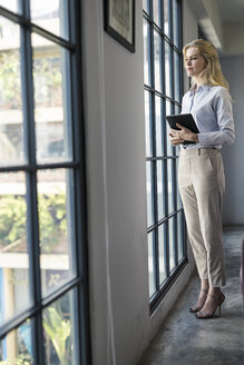 Confident businesswoman with tablet standing in office looking out of window - SBOF01584
