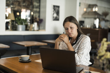 Young businesswoman in a cafe working with laptop on wooden table - SBOF01587