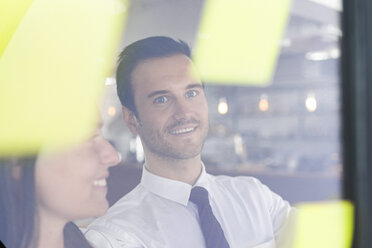 Businessman with colleague brainstorming with post-its on window front - SBOF01596