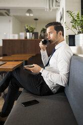 Businessman enjoying coffee and having a break on bench in cafe - SBOF01602