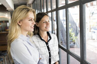 Two smiling female colleagues looking out of window - SBOF01605