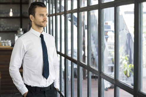 Confident businessman looking out of window - SBOF01608