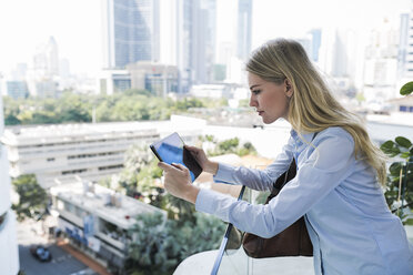 blonce woman with tablet leaning onto glass handrail in front of city skyline - SBOF01611