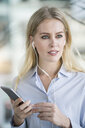 Portrait of blond woman with smartphone and earphones - SBOF01614