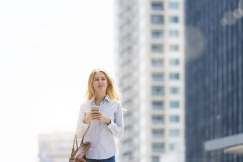 Blond woman with handbag and cell phone walking through the city - SBOF01617