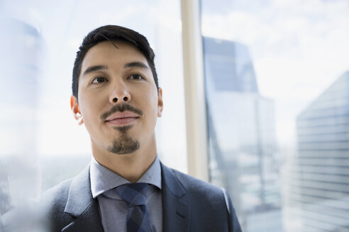 Portrait confident businessman with goatee at urban office window - HEROF05679