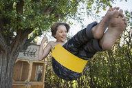 Playful boy swinging on tree swing in summer yard - HEROF05694