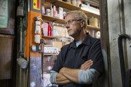 Pensive senior male mechanic looking away in workshop doorway - HEROF05709