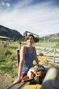 Portrait confident female farmer at truck bed on sunny farm - HEROF05724
