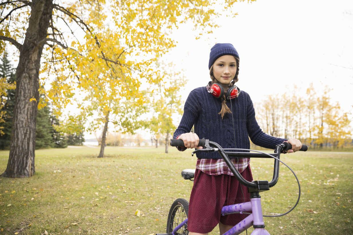 Portrait confident tween girl with headphones and bicycle in autumn park - HEROF05793 - Hero Images/Westend61