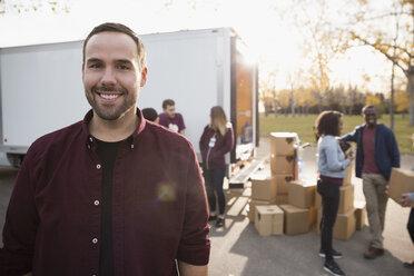 Portrait smiling male volunteer standing outside truck - HEROF05805