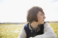 Pensive tween boy looking away in sunny field - HEROF05814