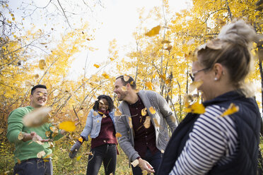 Playful friends throwing autumn leaves in woods - HEROF05820