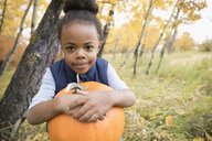 Portrait confident girl holding pumpkin in autumn woods - HEROF05823