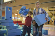 Portrait mother and son stacking large pieces in science center - HEROF05874