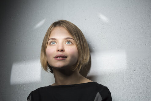 Portrait of blond young woman with bob hairdo starring at distance - VGF00202