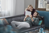 Happy couple with tablet on couch at home - RORF01577