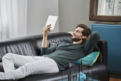 Smiling man with tablet lying on couch at home - RORF01580
