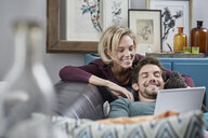 Happy couple with tablet on couch at home - RORF01583