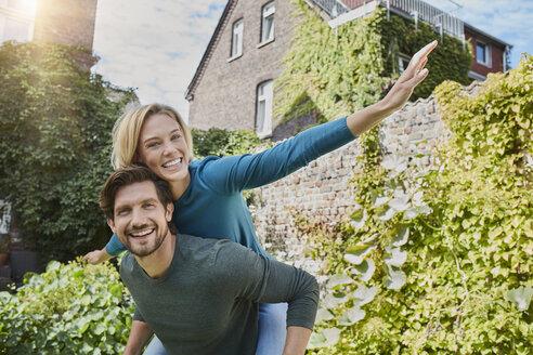 Deutschland, Nordrhein-Westfalen, Stadt Essen, Familie, Lifestyle, Paar huckepack, Haus, Garten, Immobilie - RORF01595