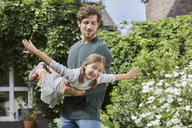 Happy father playing with daughter in garden of their home - RORF01598