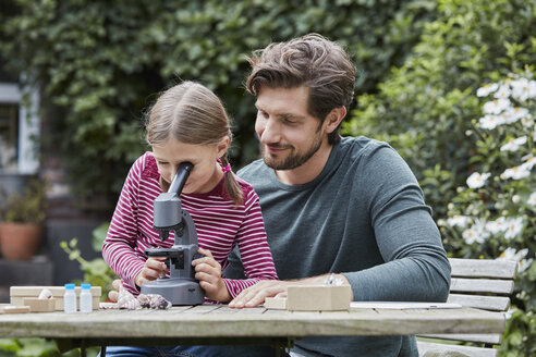 Father and daughter using microscope together at garden table - RORF01607