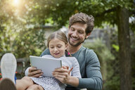 Happy father and daughter using tablet together in garden - RORF01610