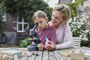 Mother and daughter using microscope together at garden table - RORF01613