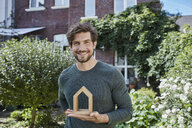Portrait of smiling man in front of his home holding house model - RORF01616