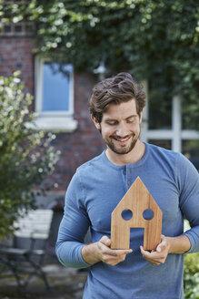 Deutschland, Nordrhein-Westfalen, Stadt Essen, Familie, Lifestyle, Mann vor Backsteinhaus mit Immobilien-Model, Haus, Immobilie - RORF01619