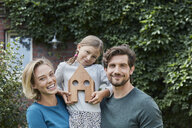 Portrait of happy family in front of their home with house model - RORF01622