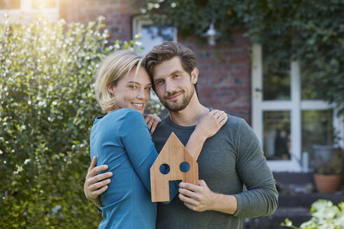 Portrait of happy couple in front of their home with house model - RORF01628