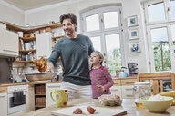 Happy father and daughter baking pancakes in kitchen at home together - RORF01631