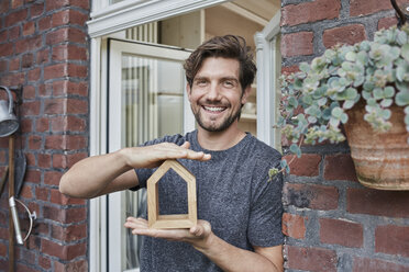 Portrait of smiling man at house entrance holding house model - RORF01634
