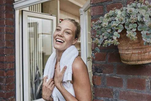 Happy sporty young woman with towel around her neck at house entrance - RORF01640