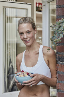 Portrait of smiling sporty young woman with muesli bowl at house entrance - RORF01643